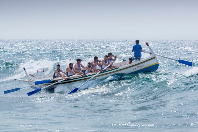 Men rowing a boat in waves.