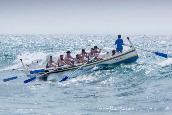 Men rowing a boat in waves.